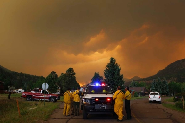 Firefighters stage in a residential area in South Fork, Colo., as they monitor a wildfire that burns west of town on Friday evening. The town was evacuated and U.S. 160 that passes through it was  ...
