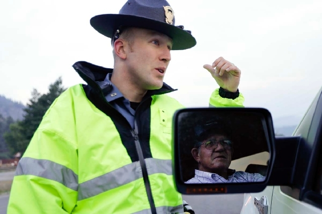 Colorado State Patrol officer Jessie Bartunek, left, speaks to a South Fork, Colo., resident who did not give his name at a checkpoint on Saturday on the outskirts of South Fork. Fire crews with t ...