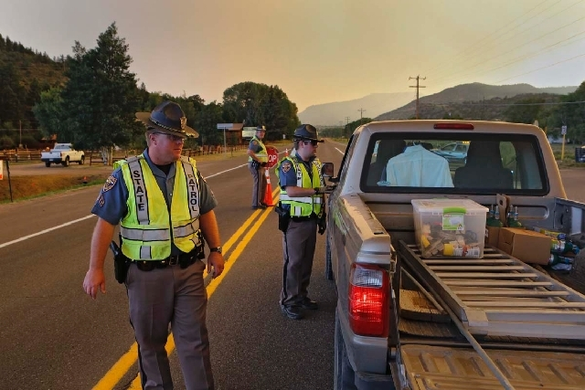Colorado State Patrol officers man a road block on U.S. 160 east of South Fork, Colo., on Friday evening. The highway was closed through South Fork and over Wolf Creek Pass because of a wildfire b ...