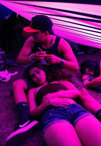 Valerie Pacheco rests in the lap of Marco Martinez during the Electric Daisy Carnival in Las Vegas on Saturday.