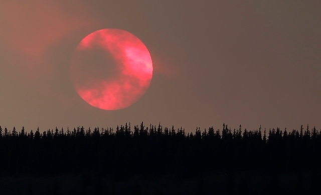 Wildfire smoke masks the sun as it sets over a ridge Saturday near South Fork, Colo.  A massive wildfire threatening a tourist region in southwestern Colorado has grown to nearly 60 square miles.