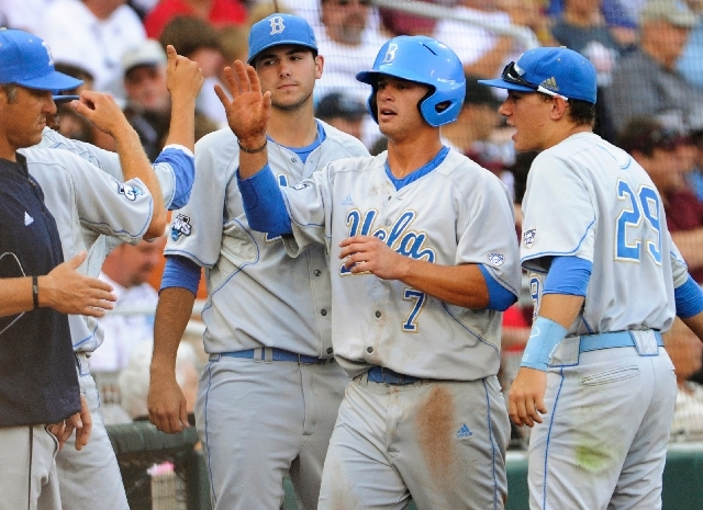 UCLA's Kevin Kramer (7) is greeted by teammates, including Ty Moore, right, after he scored against Mississippi State on a single by Pat Valaika in the first inning of Game 1 of the NCAA College W ...