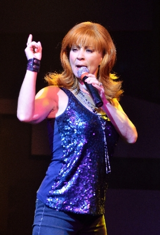"""Corrie Sachs performs as Reba McEntire during the """"Country Superstars"""" show at the V Theater in the Miracle Mile Shops."""