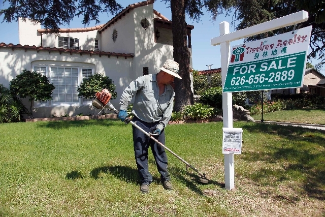 Gardener Jose Lopez trims the front lawn of a home for sale in Alhambra, Calif., in May. U.S. home prices jumped 12.1 percent in April from a year ago, buoyed by strong demand and a limited supply ...