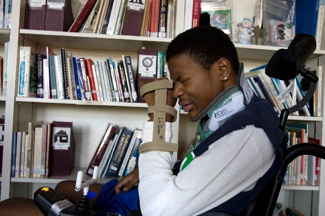 Green Valley High School senior football player LaQuan Phillips, right, who was paralyzed during a game against Centennial High School on September 5, 2008, winces in pain while in the library at  ...