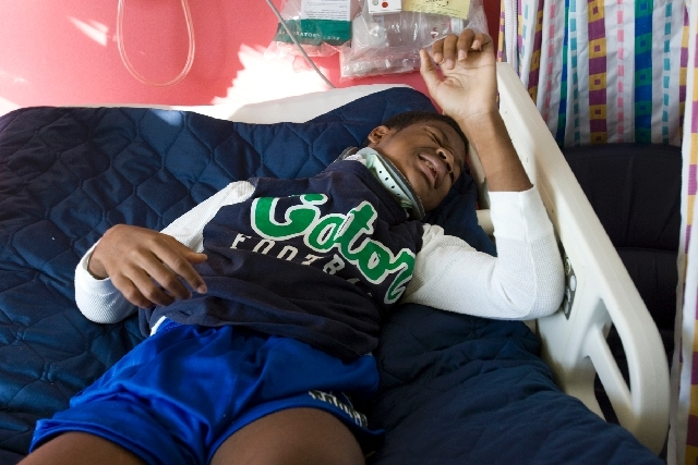 Green Valley High School senior football player LaQuan Phillips, who was paralyzed during a game against Centennial High School September 5, tries to adjust his bed using his elbow during rehabili ...