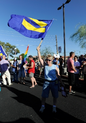 Deborah Zaring waves an equal rights flag during the Supreme Court decision celebration rally at the The Gay and Lesbian Community Center of Southern Nevada on Wednesday.