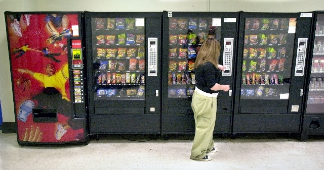 A student purchases a Pop-Tart from a school vending machine in 2006 in Wichita, Kan. High-calorie sports drinks and candy bars will be removed from school vending machines and cafeteria lines as  ...