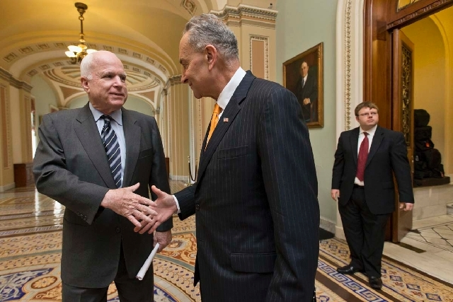 Sens. John McCain, R-Ariz., left, and Charles Schumer, D-N.Y., shake hands Thursday before the vote to pass immigration reform. The senators were two of the authors of the bill crafted by the Sena ...