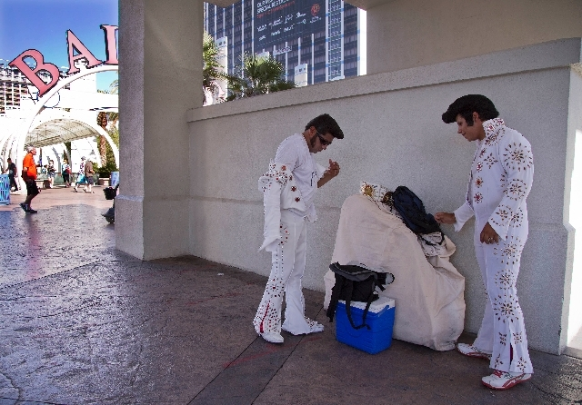 Elvis impersonators Cristian Morales, left, and Angel Figueroa pull off their jumpsuits Thursday after a day of posing with tourists for photos and tips along The Strip. Morales and Figueroa prefe ...