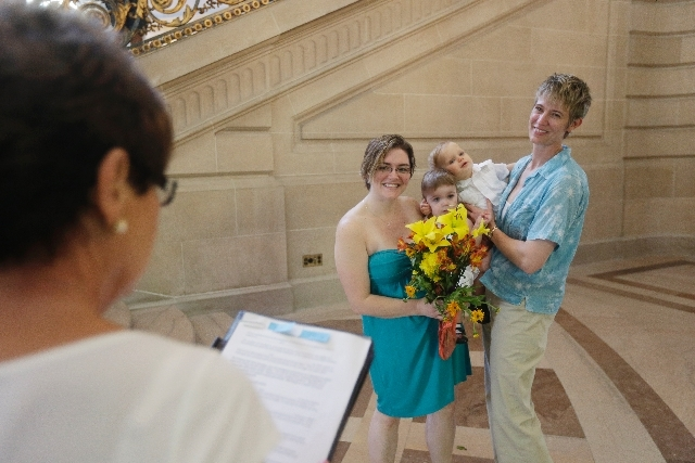 Kim (at right) and Rachel Hadley exchange wedding vows as they hold their twins.