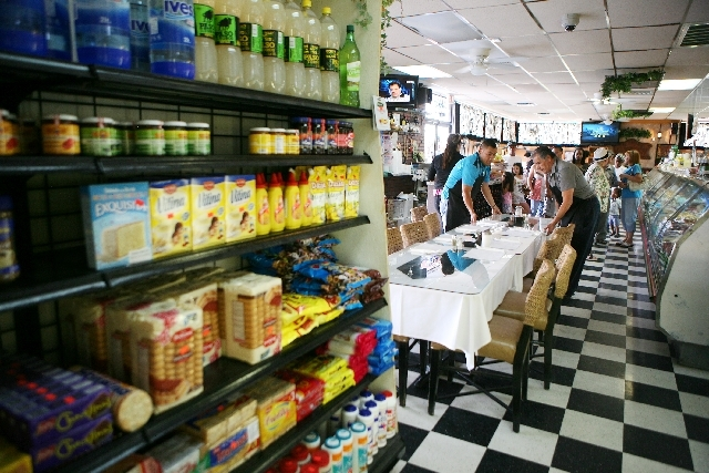 Staff members put tables together to accommodate a large party at Rincon de Buenos Aires restaurant and deli Saturday. Rincon de Buenos Aires offers a large selection of authentic Argentinian cuis ...