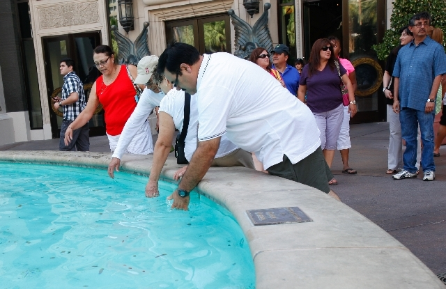 People feel the water in a fountain outside The Forum Shops at Caesars Palace on Sunday as the Strip sizzles in triple-digit temperatures.