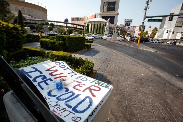 A sign lies in the trash outside Caesars Palace while few pedestrians are seen Sunday as the temperature approaches 117 degrees on the Strip. The high temperature tied the record set in 1942 and 2005.