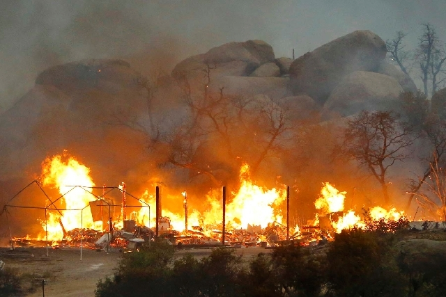 Homes burn as the Yarnell Hill Fire burns in Glenn Ilah on Sunday near Yarnell, Ariz. The fire started Friday and spread to 2,000 acres on Sunday amid triple-digit temperatures, low humidity and w ...