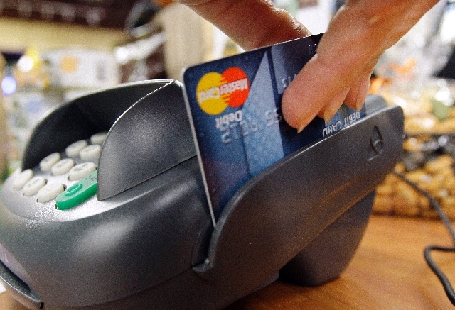 In this file photo, a customer swipes a MasterCard debit card through a machine while checking-out.