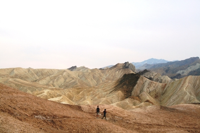 Hikers head across the badlands below Zabriskie Point in Death Valley National Park, Calif.