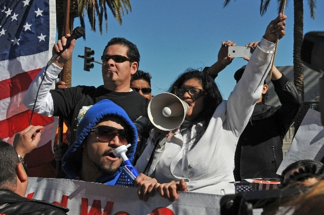 Rosemary Flores addresses a rally crowd with a megaphone. Flores is creating an organization, Coming Out of the Shadows, to collect stories of immigrants to present to Congress.