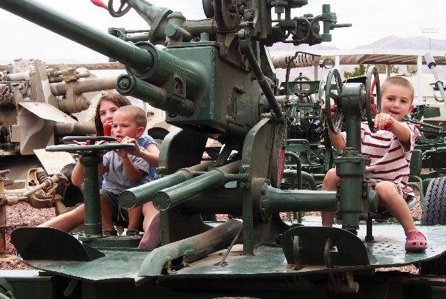Grace DeRosa, 9, holds her little brother Xavier, 2 1/2, as another brother, Anthony, 6, operates controls of a World War II Soviet 37mm Anti-Aircraft gun at the Threat Training Facility, nickname ...
