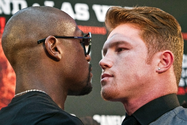 """Floyd Mayweather, left, poses in a face-off with Saul """"Canelo"""" Alvarez during a boxing news conference on Monday, June 24 at New York's Times Square. MayWeather and Alvarez kicked-off an 11-city p ..."""