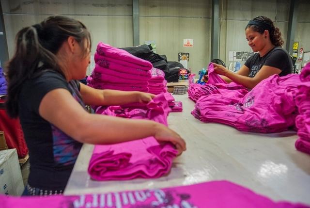 Eagle Promotions employees Elda Lopez, left, and Melina Alvarado fold shirts inside the production room.