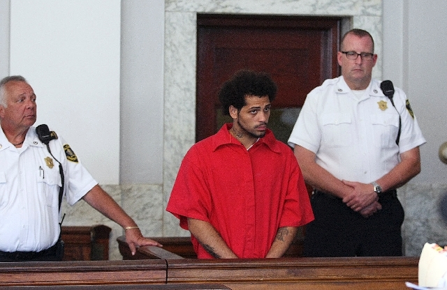 Carlos Ortiz, left, stands in Attleboro District Court for his arraignment on weapons charges, June 28 in Attleboro, Mass.
