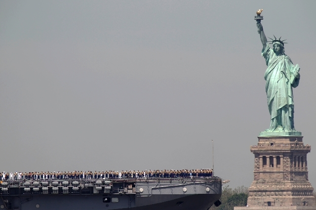 Sailors stand on deck of the USS Iwo Jima as it passes Liberty Island and the Statue of Liberty during Fleet Week in New York in 2011.