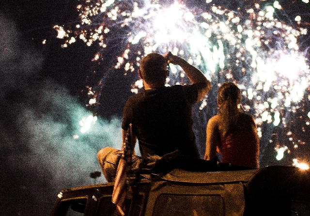 From left, David and Romina Muller sit on the roof of their car and watch the Fourth of July fireworks display at Texas Station in 2011.