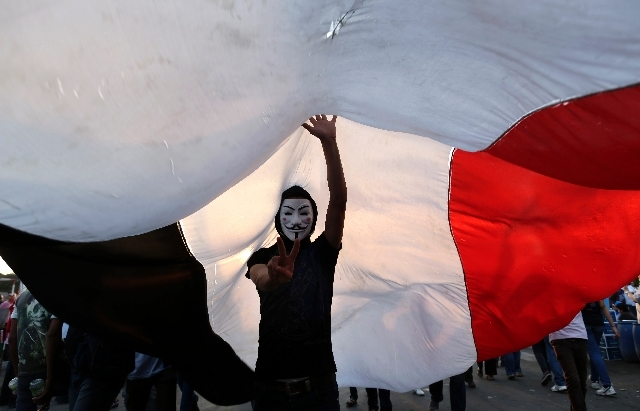 An opponent of Egypt's Islamist President Mohammed Morsi wearing a Guy Fawkes mask flashes the victory sign under a large Egyptian national flag during a protest outside the presidential palace, i ...