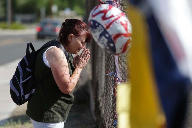 Deborah Heinemann pays her respects at a makeshift memorial outside the Granite Mountain Interagency Hotshot Crew fire station on Tuesday in Prescott, Ariz., honoring 19 firefighters killed battli ...