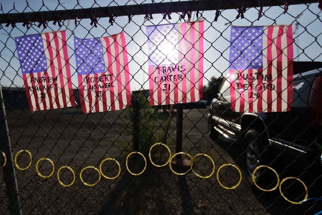Flags with the names of the fallen firefighters hang at a makeshift memorial outside the Granite Mountain Interagency Hotshot Crew fire station on Tuesday in Prescott, Ariz. The elite crew of fire ...