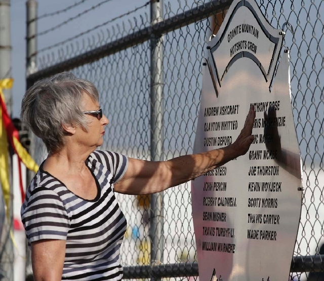 Georgia Johnson, of Prescott, Ariz., pays her respects Tuesday at a plaque honoring 19 firefighters killed battling a wildfire near Yarnell on Sunday.