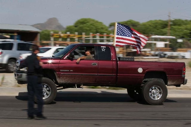 A truck with an American flag drives by a makeshift memorial outside the Granite Mountain Interagency Hotshot Crew fire station on Tuesday in Prescott, Ariz., honoring 19 firefighters killed battl ...