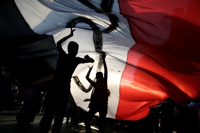Opponent of Egypt's Islamist President Mohammed Morsi hold a large Egyptian national flag during a protest outside the presidential palace, in Cairo, Egypt, Tuesday. Egypt was on edge Tuesday foll ...