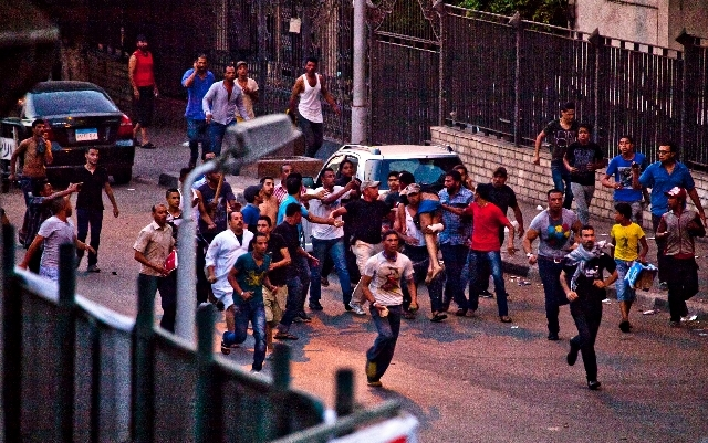 Protesters run with an injured comrade following clashes in the Kit Kat neighborhood of Giza, Egypt, Tuesday.  With a military deadline for intervention ticking down, hundreds of thousands of prot ...