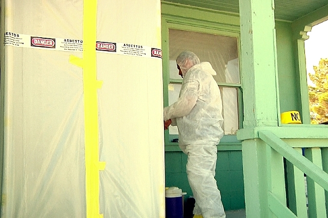 A worker from A&B Environmental prepares to remove lead paint and asbestos from a historic railroad cottage at the Clark County Museum on Tuesday. The cottage was one of many built by the Union Pa ...