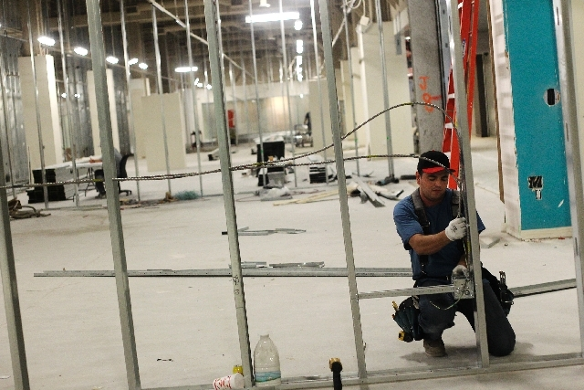 Construction worker Elvis Arostegui, right, runs electrical conduit at a World Market Center showroom in Las Vegas on July 2.