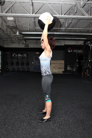 Stand with the feet hip-width apart. Dead lift the medicine ball and hold it overhead with the core tight and the back straight.