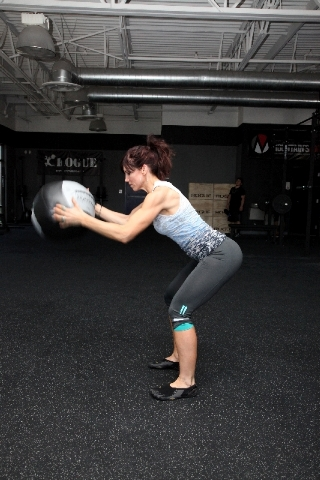 Hinging at the hips, forcefully slam the ball onto the ground using the force generated by the hips as well as the lats and arms.The major form flaw is to not use the hips. The hips allow fo ...