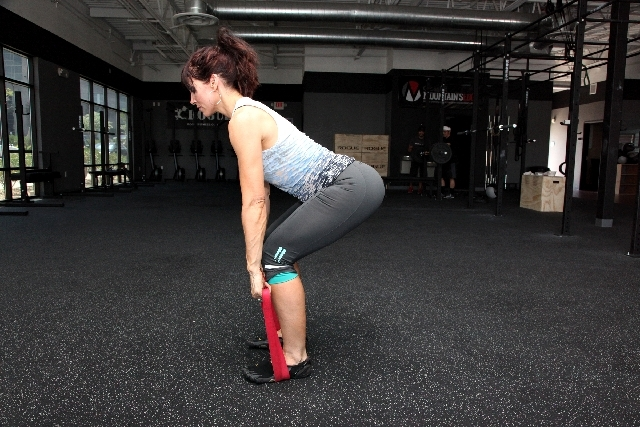 Lay the jump-stretch band on the ground. Stand on top of it with both feet hip width apart and toes pointed straight. Hold onto each end with the hands. From this position, get into the bottom pos ...