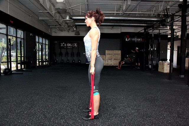 Contract the glutes and stand while holding onto the ends of the jump-stretch band. Hinging at the hip and keeping the back straight, return to the starting position. Common form flaws are for the ...