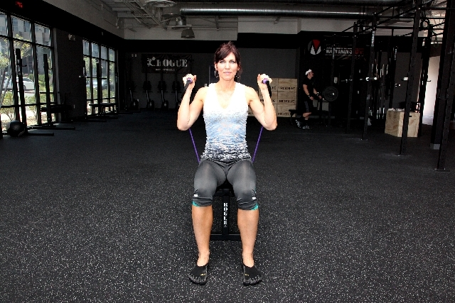 Sit on a bench or chair holding the handles of the resistance band that is laced under the bench to use it as an anchor point. Sit with the back straight, core tight. Position the hands at shoulde ...