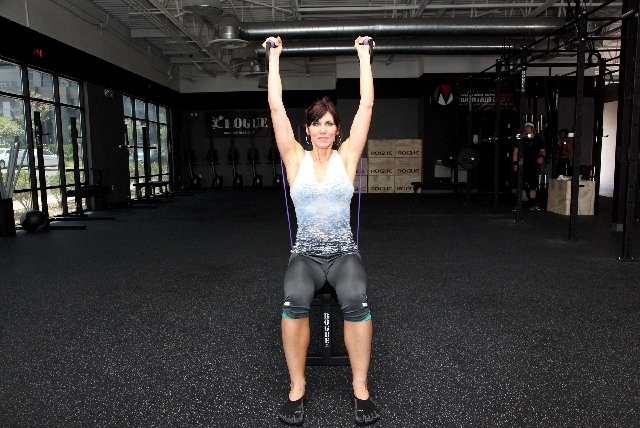 Contract the core and press the hands overhead with the palms of the hands still facing each other. Return to the starting position.