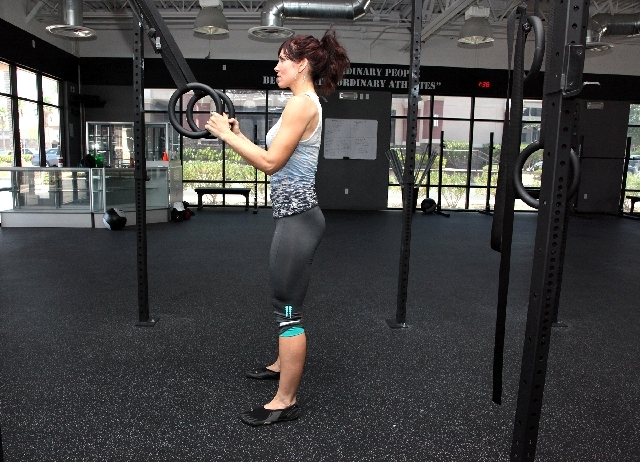 ASSISTED SQUATS START: Stand with the feet at shoulder width and toes pointed slightly outward. Hold the rings or handles so the hands are at chest level and the straps are taut. Contract the core ...