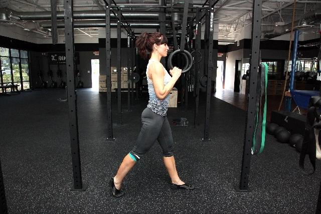 ASSISTED LUNGES START: Stand under the anchor point of the rings. Grasp the rings at shoulder height so the straps are taut. Assume a lunge position with the core tight and torso upright.