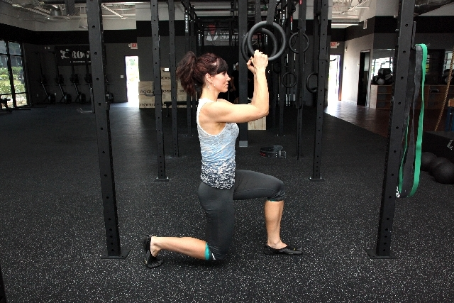 ASSISTED LUNGES ACTION: Allowing the knees to bend, lower the hips straight down so the back shin is parallel to the ground. Contract the glutes, push though the heel of the front foot and the toe ...