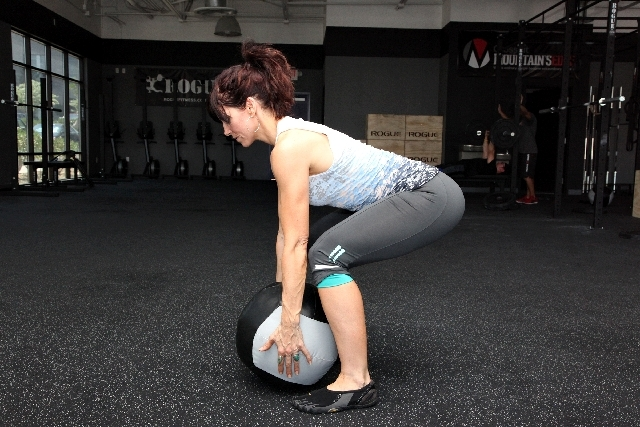 With the medicine ball on the ground, stand over the ball and position the feet at hip width. Straighten the feet. Contract the glutes and core and straighten the back. Placethe head in a ne ...