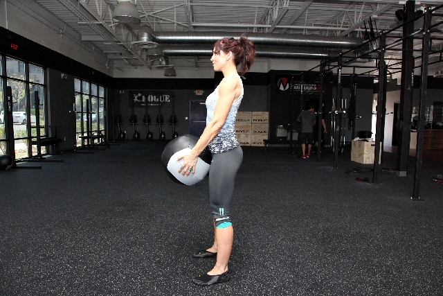Contract the glutes and stand up with the medicine ball.Keep the back straight by holding the core tight. Keeping the spine straight means keeping the neck straight, too. If you are having t ...