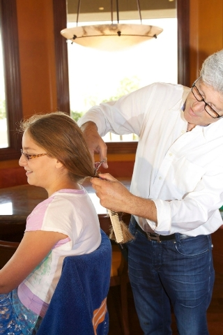 Allison Stone, 10, gets her hair cut for Locks of Love in her Summerlin home July 1 by hair stylist Michael Schwert. This was Allison's third Locks of Love haircut.