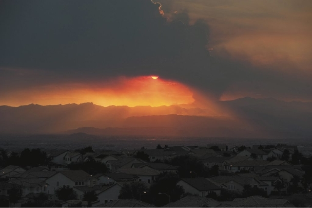 In this view looking west from Henderson, the sun sets behind a column of smoke created by a fire burning in the Carpenter Canyon area of Mt. Charleston on Tuesday. According to the BLM, the fire  ...